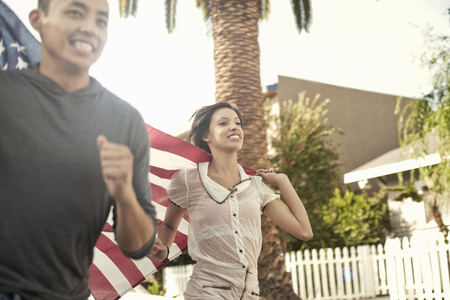 Couple running along street holding up the American flag LANG_EVOIMAGES