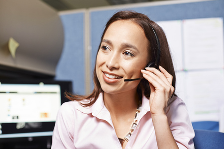 handsfree telephones: Young female office worker using headset in office