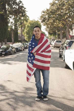 suburbia: Portrait of mid adult man standing on street wrapped in American flag LANG_EVOIMAGES