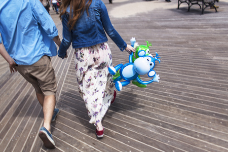 woman hanging toy: Cropped rear view of couple holding hands on boardwalk
