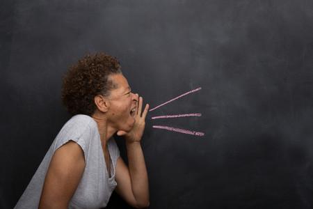 exerting: Senior woman in front of blackboard pretending to shout