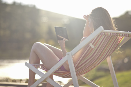information superhighway: Young woman on deckchair using digital tablet