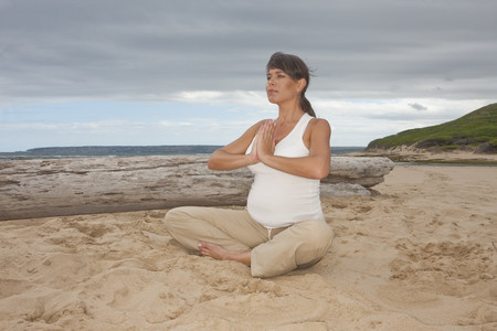Pregnant mid adult woman practicing yoga on beach LANG_EVOIMAGES