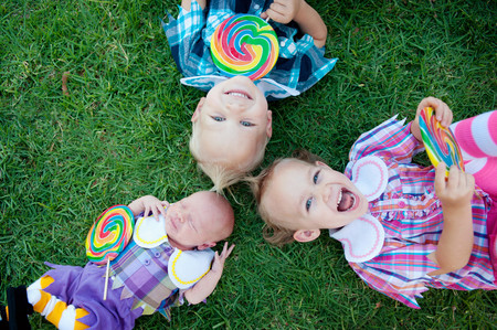 Siblings with lollipops lying on grass LANG_EVOIMAGES