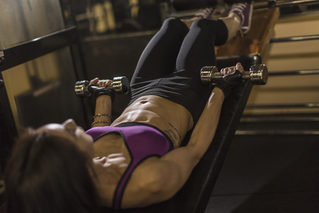 Mid adult woman using dumbbells on weight bench LANG_EVOIMAGES