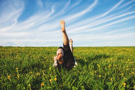pubertad: Mujer joven tumbado en la hierba con las piernas levantadas