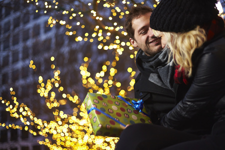give out: Young couple exchanging gifts next to outdoor xmas lights