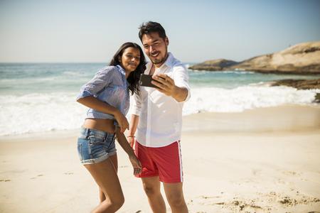 Couple taking selfie on smartphone, Arpoador beach, Rio De Janeiro, Brazil