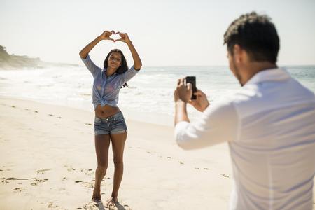 Mid adult man photographing girlfriend on smartphone, Arpoador beach, Rio De Janeiro, Brazil LANG_EVOIMAGES
