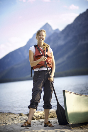 Portrait of female canoeist by lake, Grand Tetons, Wyoming, USA LANG_EVOIMAGES