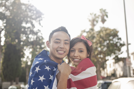 pubertad: Retrato de una pareja de pie en la calle envuelto en bandera americana LANG_EVOIMAGES