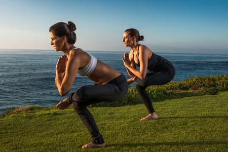 two persons only: Women on cliff, in yoga positions LANG_EVOIMAGES