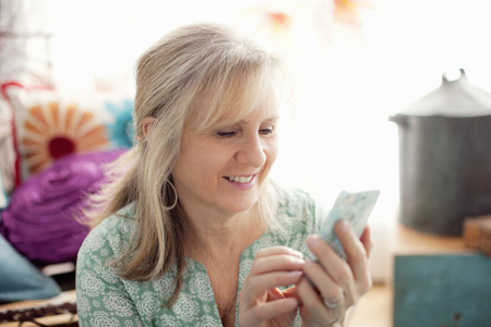 Mature woman texting on cellphone in living room LANG_EVOIMAGES