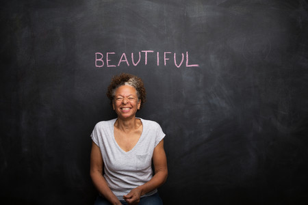 shutting: Senior woman in front of blackboard and the word beautiful LANG_EVOIMAGES