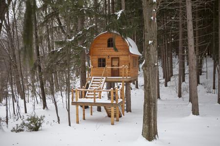 Hand built wooden chalet on stilts in snow covered forest LANG_EVOIMAGES