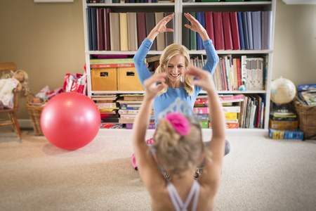 Mother and young daughter practicing ballet in sitting room