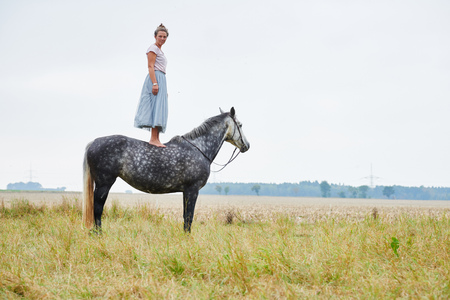Woman in skirt standing on top of dapple grey horse in field