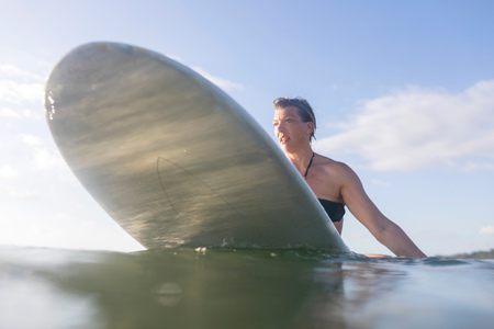 Woman straddling surfboard in sea, Nosara, Guanacaste Province, Costa Rica LANG_EVOIMAGES