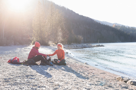 anorak: Two female hikers taking a break on lakeside in Bavarian Alps