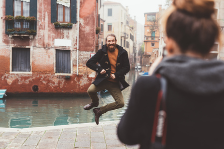 venice: Woman photographing man jumping by canal, Venice, Italy LANG_EVOIMAGES