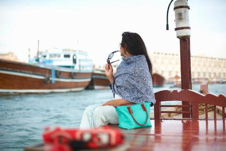 Female tourist sitting on waterfront watching boats on creek, Dubai, United Arab Emirates