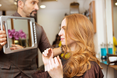 hairdresser: Hairdresser showing customer styled long red hair in salon LANG_EVOIMAGES