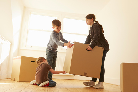 cardboard only: Girl and two brothers lifting cardboard box in new home