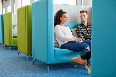common room: University students relaxing in modern cubicle seating area LANG_EVOIMAGES