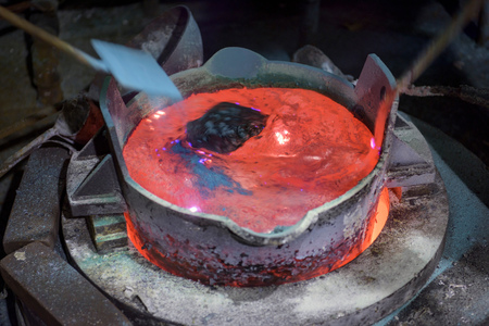 plied: Workers stirring molten aluminium alloy in precision casting factory
