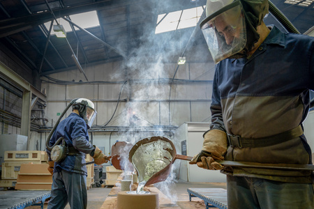 boiler suit: Workers pouring molten aluminium into moulds in precision casting factory