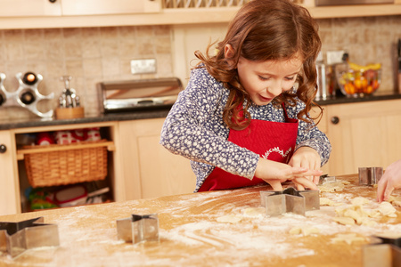 Girl baking star shape pastry at kitchen table