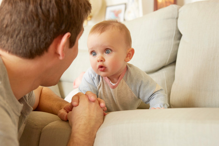Cute blue eyed baby girl on sofa staring at her father LANG_EVOIMAGES