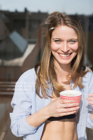 Portrait of beautiful woman wearing open shirt holding coffee  at window LANG_EVOIMAGES