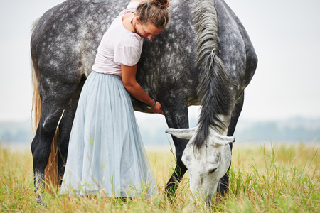 Woman in skirt with arms around dapple grey horse in field LANG_EVOIMAGES