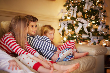 Boy and girls in striped pyjamas on sofa at christmas LANG_EVOIMAGES
