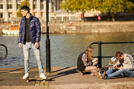 Three friends fooling around beside river, young man on skateboard, Bristol, UK