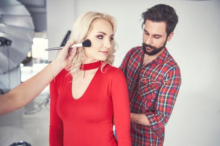 Male photographer and make up artist preparing female model for studio photo shoot