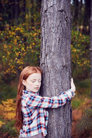 Young girl, hugging tree LANG_EVOIMAGES