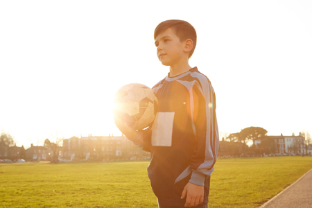 Boy football player holding ball in sunlit park LANG_EVOIMAGES