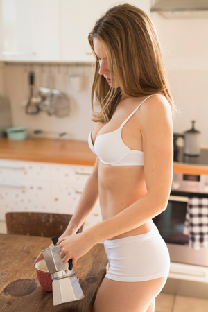 Beautiful woman in kitchen wearing bra and knickers pouring espresso LANG_EVOIMAGES