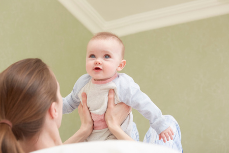 Women holding up baby daughter LANG_EVOIMAGES