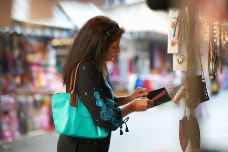 Mature female tourist looking beaded purse on market stall, Sharjah, United Arab Emirates LANG_EVOIMAGES