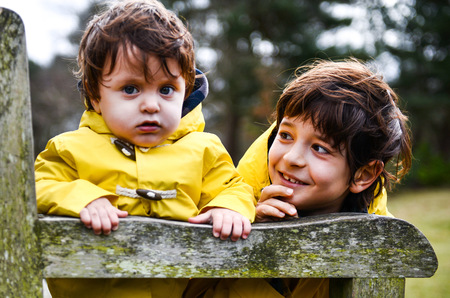 Portrait of baby boy and big brother in yellow anoraks on park bench