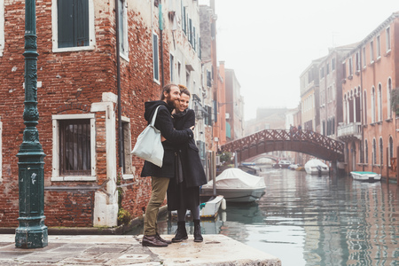 Couple hugging on misty canal waterfront, Venice, Italy