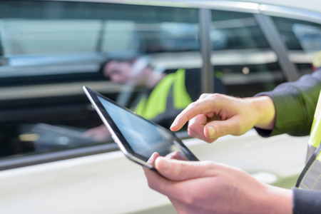 communication skills: Apprentice car inspector using tablet in car factory, close up LANG_EVOIMAGES