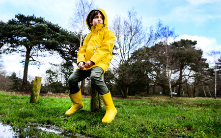 Boy in yellow anorak sitting on park fencepost LANG_EVOIMAGES
