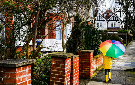 Rear view of boy in yellow anorak carrying umbrella along street