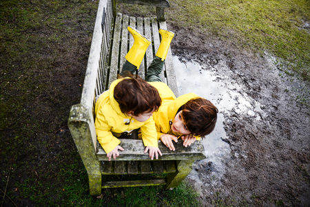 Overhead view of baby boy and brother in yellow anoraks on park bench LANG_EVOIMAGES