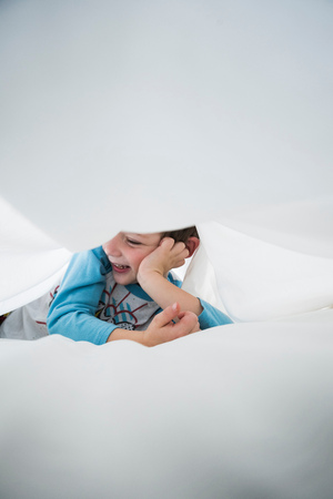 concealment: Boy lying on side between white bed sheets