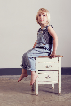 Girl sitting on old cabinet looking away